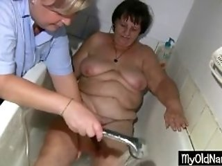 Hairy granny is washed and caressed in the bath tube by BBW