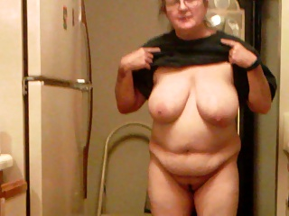 Exposed and unaware wife Cora, naked in the kitchen.