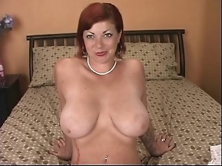 Sexy busty mature redhead plays with a vibrator on the bed